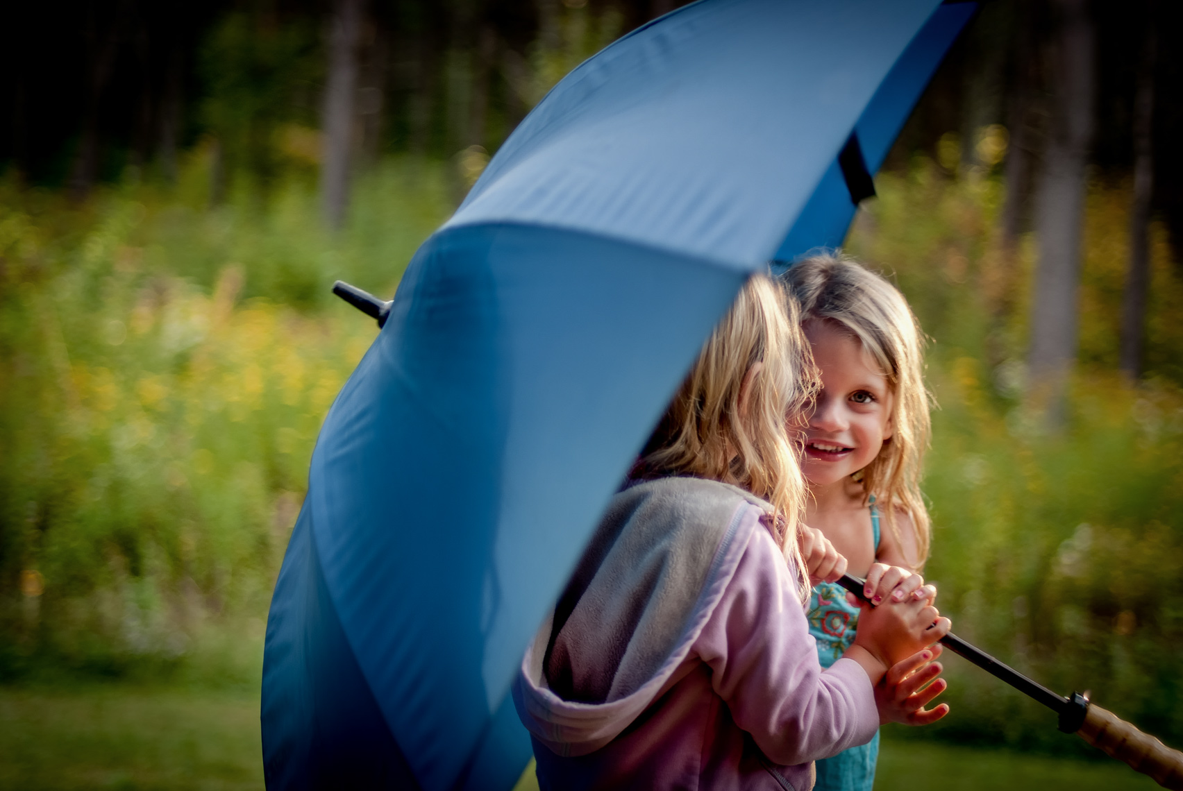 Sisters playing with umbrella